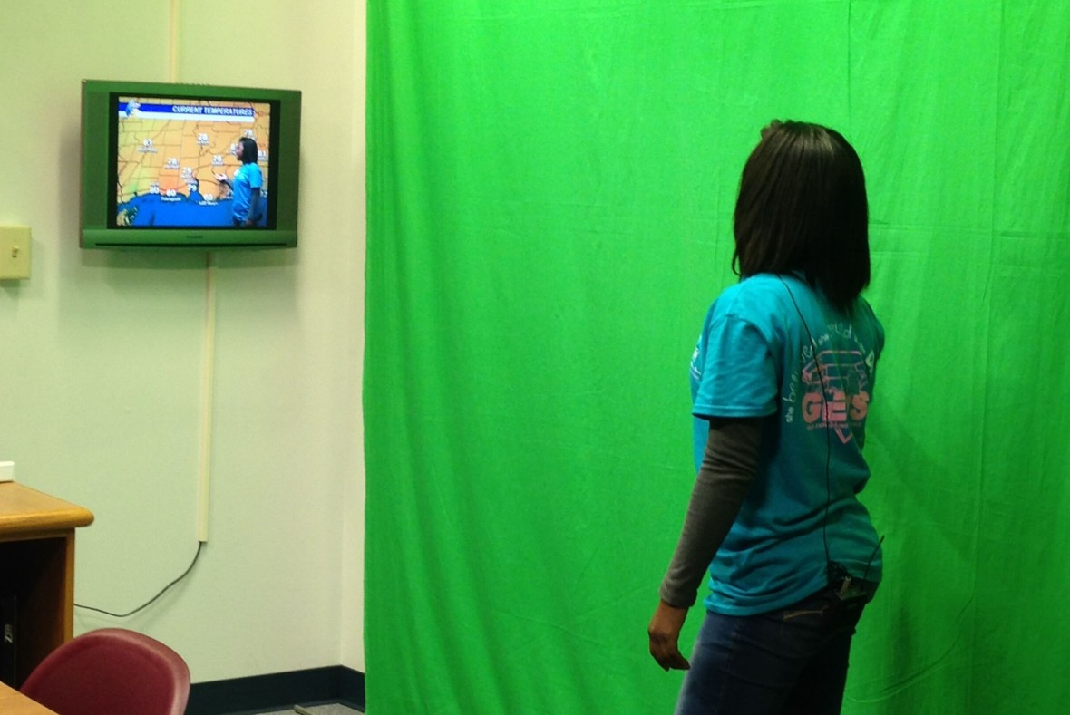 A student stands in front of a green screen and sees herself forecasting the weather on a television.