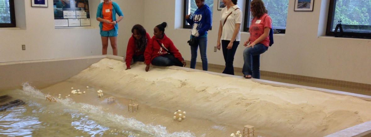 Students and instructors test the stability of structures at the edge of a wave pool.